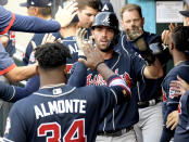 Atlanta Braves' Dansby Swanson, center, celebrates with Abraham Almonte (34) after scoring during the fourth inning of the first game of a baseball doubleheader against the New York Mets, Monday, July 26, 2021, in New York. (AP Photo/Bill Kostroun)