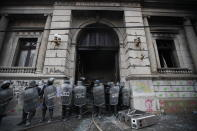 Police surround the Congress building after protesters set a part of it on fire, in Guatemala City, Saturday, Nov. 21, 2020. Hundreds of protesters were protesting in various parts of the country Saturday against Guatemalan President Alejandro Giammattei and members of Congress for the approval of the 2021 budget that reduced funds for education, health and the fight for human rights. (AP Photo/Moises Castillo)