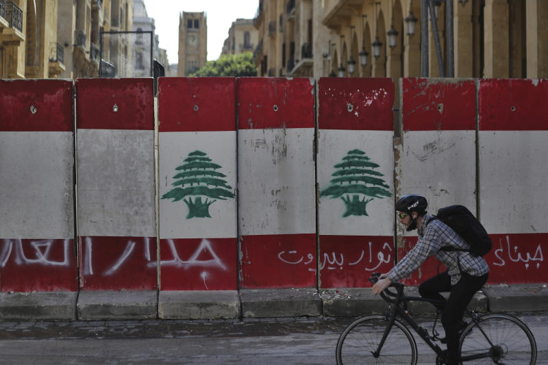 """A man rides his bicycle next to a concrete wall installed by authorities to blocks a road leading to the parliament building, in downtown Beirut, Lebanon, Friday, Jan. 24, 2020. Arabic on the wall reads """"wall of shame, left, Beirut rebels, center, Cowards."""" As cement barricades come up across the capital, blocking the path to major government buildings, Lebanese protesters vowed to continue taking to the street on the 100-day anniversary of the anti-government protests. (AP Photo/Hassan Ammar)"""