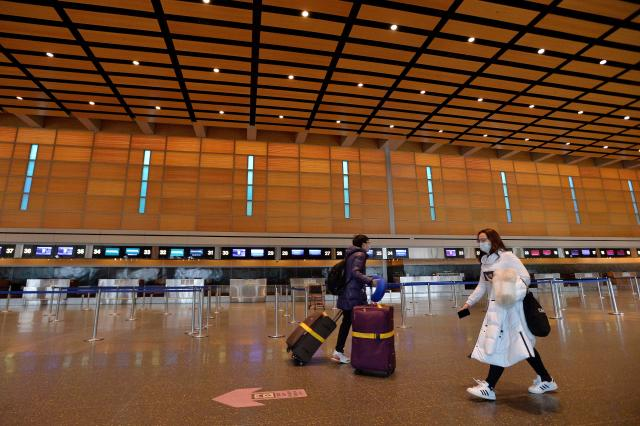 Travelers walk through an almost empty departures area at the international terminal at Logan International Airport in Boston on Friday. (Joseph Prezioso / AFP via Getty Images)