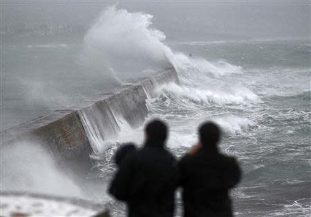 Waves crash over the breakwater of Saint Evette harbour at Esquibien in Brittany as an Atlantic storm hits western France
