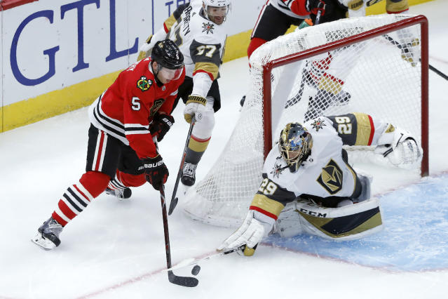 Vegas Golden Knights goaltender Marc-Andre Fleury (29) poke-checks the puck away from Chicago Blackhawks defenseman Connor Murphy during the first period of an NHL hockey game Tuesday, Oct. 22, 2019, in Chicago. (AP Photo/Charles Rex Arbogast)
