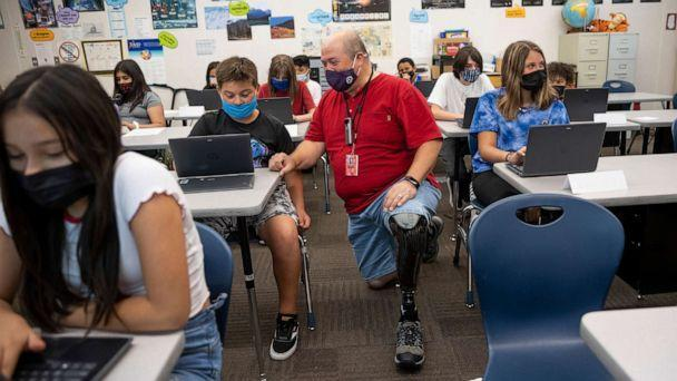 PHOTO: Bill Coleman, a sixth grade teacher, speaks with Jerry Oyler during class at Nibley Park School in Salt Lake City on Tuesday, Aug. 24, 2021. (Spenser Heaps/The Deseret News via AP, FILE)