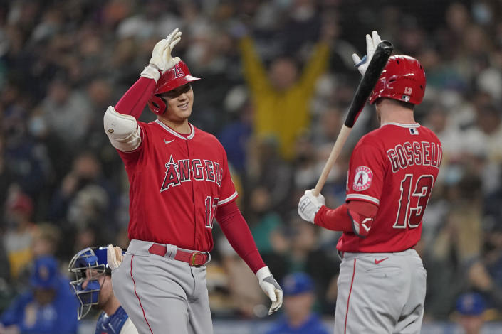 Los Angeles Angels' Shohei Ohtani, left, is greeted at the plate by Phil Gosselin (13) after Ohtani hit a solo home run during the first inning of a baseball game against the Seattle Mariners, Sunday, Oct. 3, 2021, in Seattle. (AP Photo/Ted S. Warren)