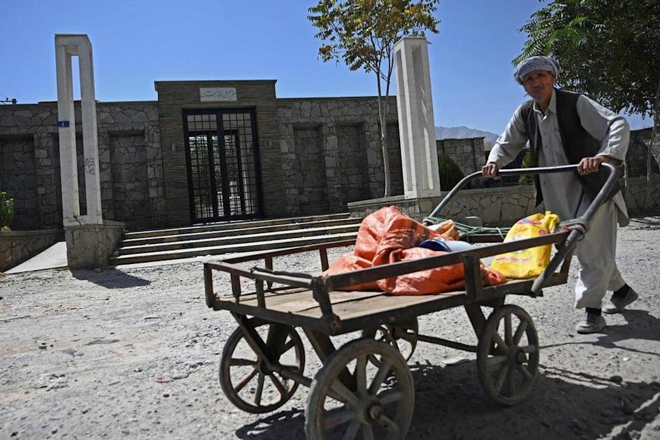 A man pushes his handcart past the main entrance of the closed National Museum in Kabul on Wednesday  (AFP via Getty Images)