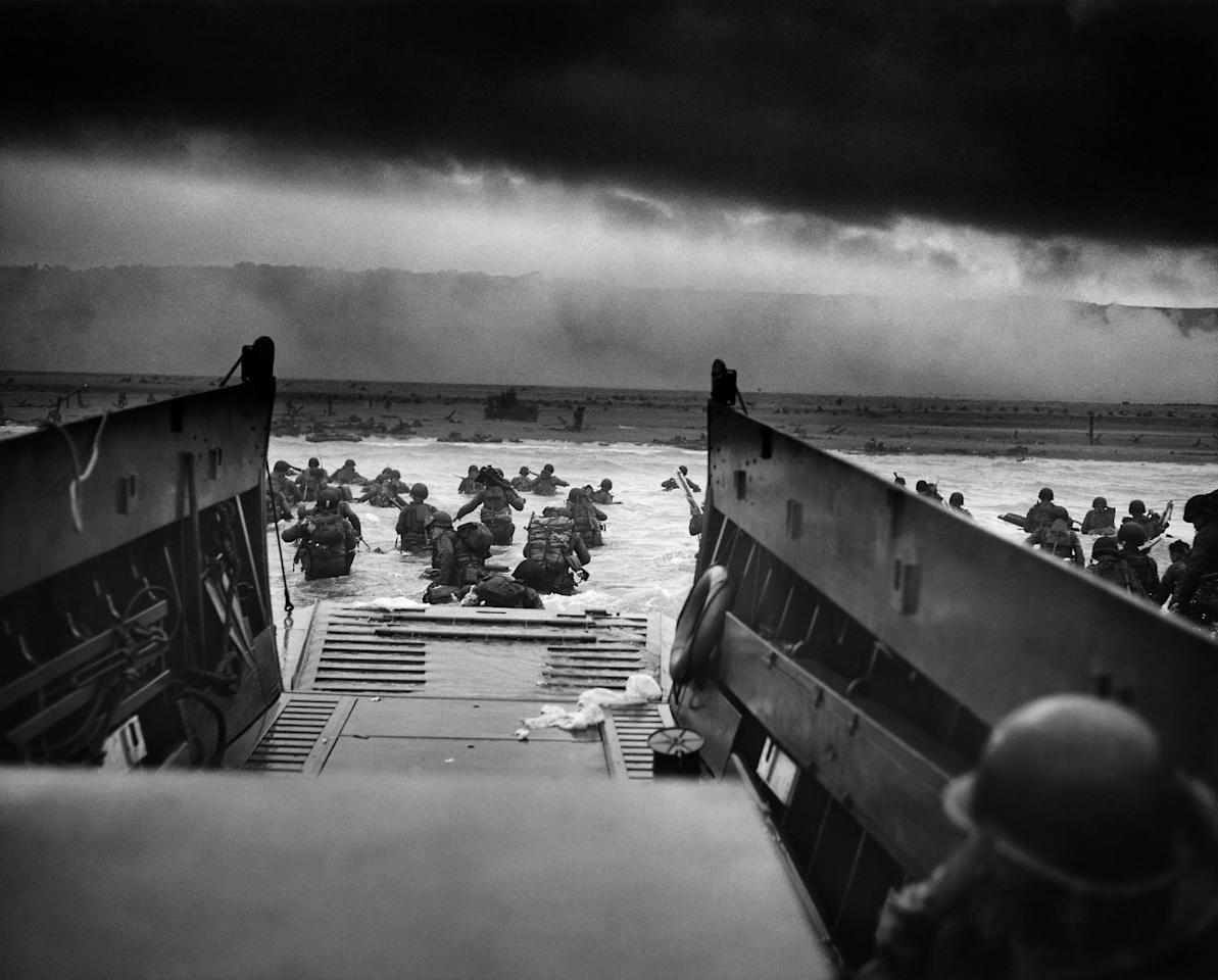 <p>U.S. troops wading through water after reaching Normandy, France, and landing on Omaha Beach on D-Day, June 6, 1944. (Photo: Universal History Archive/UIG via Getty Images) </p>