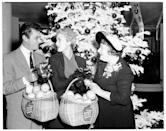 <p>Ivy Wilson, President of the Women's Press Club of Hollywood, presents gift baskets to the Hollywood power couple at an award ceremony in 1953.</p>