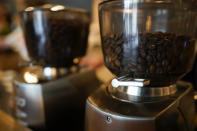 Coffee beans are seen in grinders at Vigilante Coffee, Wednesday, Sept. 1, 2021, in College Park, Md. A confluence of supply chain problems, drought, frost and inflation all point to the price of your cup of morning coffee going up. The tricky part is trying to figure when — and how much. A sustained drought followed by two July frosts blew a hole in Brazil's coffee output, sending futures contract prices for the popular Arabica bean to near seven-year highs. (AP Photo/Julio Cortez)