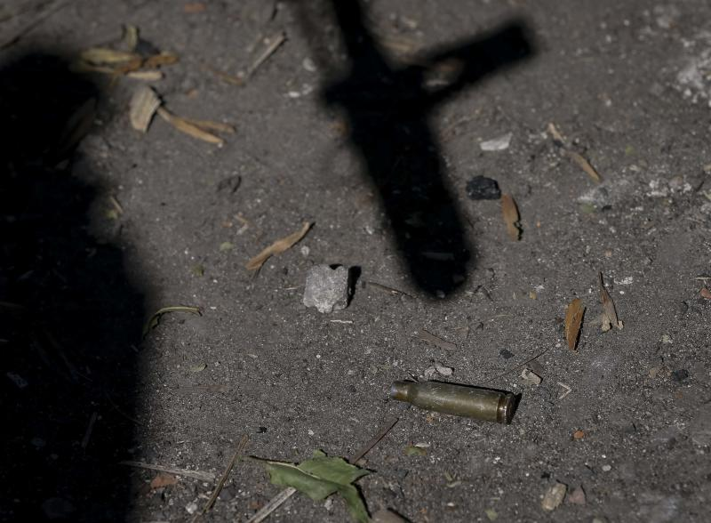 The shadow of a gun points to an expended cartridge on the ground at a checkpoint near Debaltseve