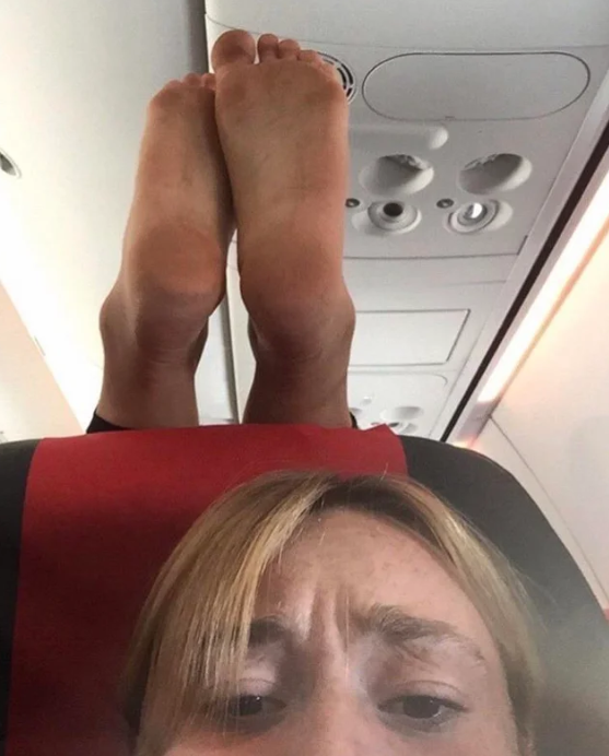 The woman is pictured frowning as the other passenger's feet dangle just above her head.Source: Reddit