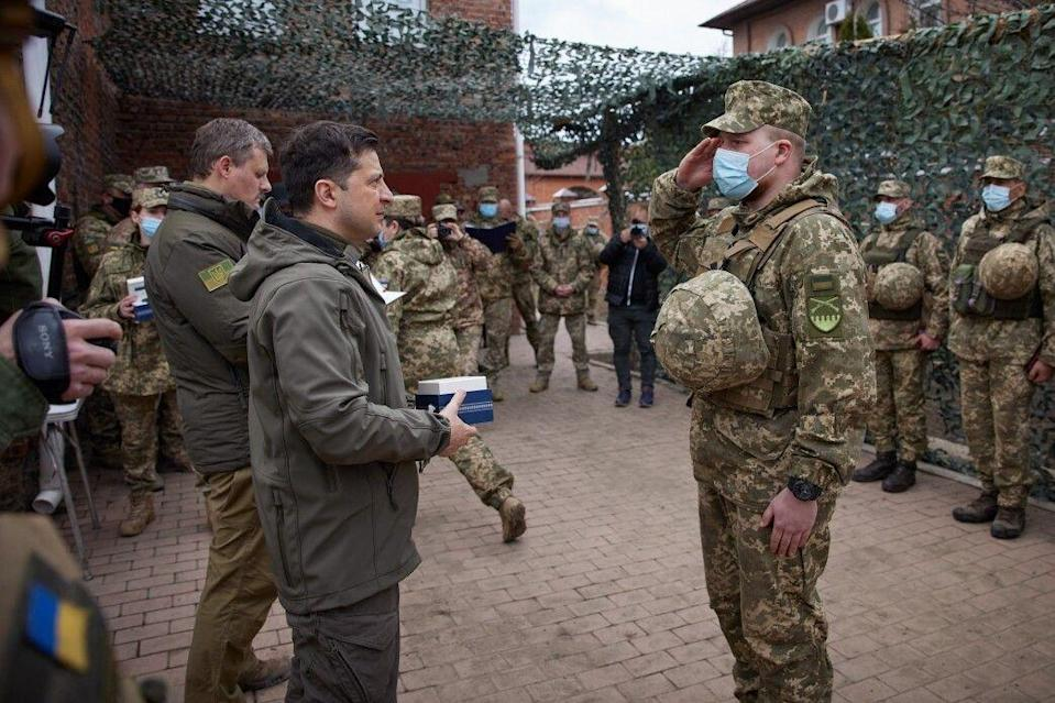 """DONBASS, UKRAINE - APRIL 08: (----EDITORIAL USE ONLY â MANDATORY CREDIT - """"UKRAINIAN PRESIDENCY / HANDOUT"""" - NO MARKETING NO ADVERTISING CAMPAIGNS - DISTRIBUTED AS A SERVICE TO CLIENTS----) Ukrainian President Volodymyr Zelensky (L) salutes a soldier during his visit to a front in Donbass, Ukraine on April 08, 2021. (Photo by Presidency of Ukraine / Handout/Anadolu Agency via Getty Images) (Photo: Anadolu Agency via Anadolu Agency via Getty Images)"""