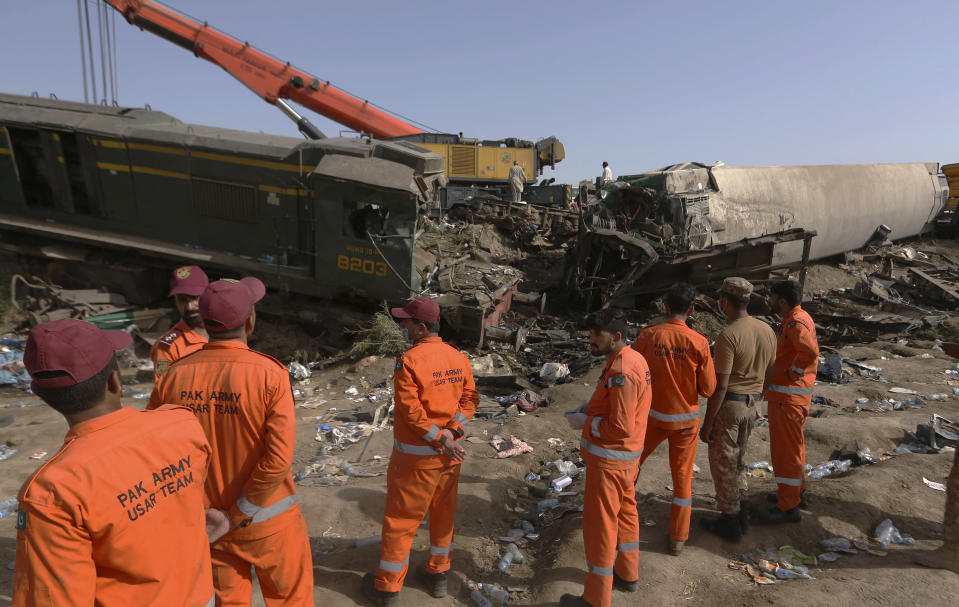 Soldiers arrive to conduct rescue operation to clear the track at the site of a train collision in the Ghotki district, southern Pakistan, Tuesday, June 8, 2021. The death toll from a deadly train accident in southern Pakistan jumped to dozens on Tuesday after rescuers pulled a dozen more bodies from crumpled cars of two trains that collided on a dilapidated railway track a day ago, an official said, as rescue work continued even 24 hours after the incident to find any survivors. (AP Photo/Fareed Khan)