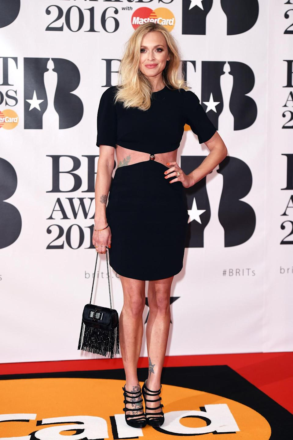 <p>Showing off her tats and taut tum with a cutaway midriff number, you would never know the former Radio 1 DJ is a mum of two. <i>[Photo: Rex]</i></p>