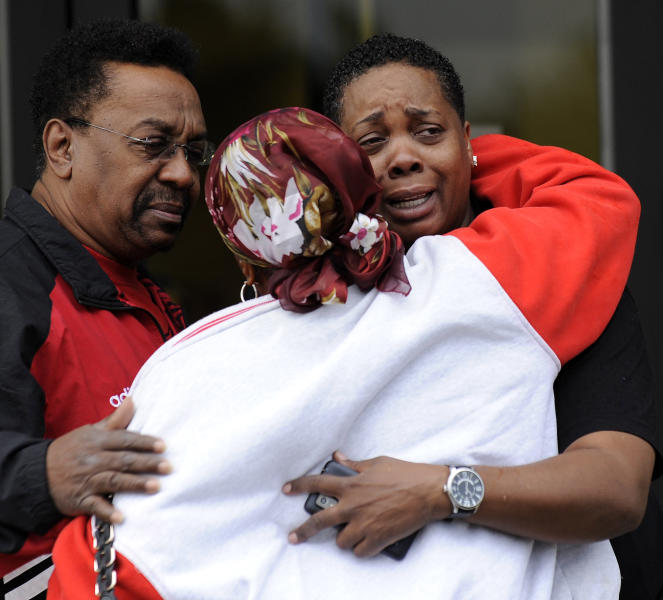 Employees hug in front of the UAW Local 7 hall across the street from Chrysler Jefferson North Assembly plant in Detroit on Thursday, Sept. 20, 2012 after a factory employee fatally stabbed his co-worker at Chrysler Group LLC's Jefferson North Assembly Plant. Detroit police Inspector Dwane Blackmon says the suspect fled the Jefferson North plant Thursday morning and shot himself to death at nearby Belle Isle Park. (AP Photo/Detroit News, David Coates) DETROIT FREE PRESS OUT; HUFFINGTON POST OUT. MANDATORY CREDIT