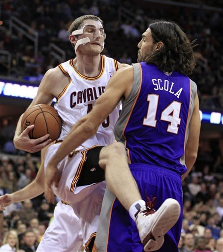 Cleveland Cavaliers' Tyler Zeller, left, gets a rebound ahead of Phoenix Suns' Luis Scola during the second quarter of an NBA basketball game Tuesday, Nov. 27, 2012, in Cleveland. (AP Photo/Tony Dejak)