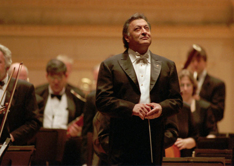 "FILE - In this April 24, 1996 file photo, conductor Zubin Mehta and the Israel Philharmonic enjoy the applause after the performance at New York's Carnegie Hall. When Mehta joined the Israel Philharmonic Orchestra in 1969, Lahav Shani wasn't even alive. Now, at the age of 30, the Israeli wunderkind is poised to succeed his mentor at the helm of the acclaimed symphony. Mehta, 83, is set to step down late this year after leading the orchestra for half a century and serving as its ""music director for life"" since 1981. (AP Photo/Paul Hurschmann, File)"