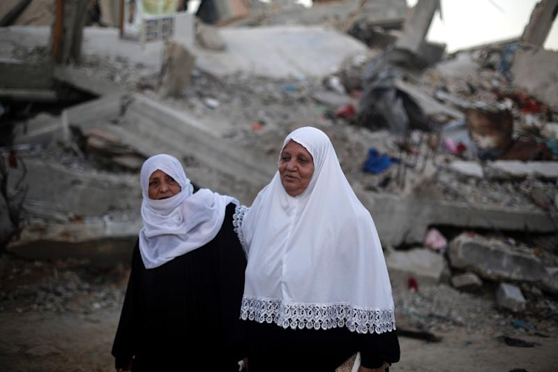 Palestinian women walk past the rubble of buildings that were destroyed during the 50-day war between Israel and Hamas militants in the summer of 2014, in Gaza City's al-Shejaiya neighbourhood, on March 31, 2015 (AFP Photo/Mohammed Abed)
