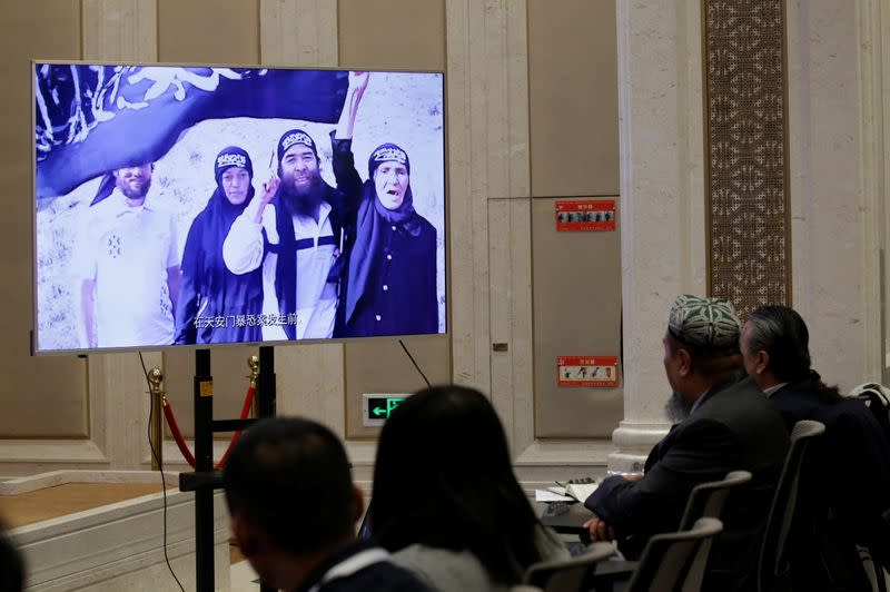 "An image of what has been described as scenes of past violence is displayed in excerpts from a documentary ""Fighting Terrorism in Xinjiang"" at a news conference in Beijing"