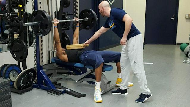 Grizzlies strength and conditioning coach Chattin Hill works with a bench-pressing Vince Carter on Wednesday night. (Michael Lee/The Vertical)