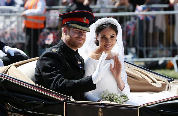 Prince Harry, Duke of Sussex, and Meghan, Duchess of Sussex, wave from the Ascot Landau Carriage during their carriage procession on Castle Hill outside Windsor Castle in Windsor, on May 19, 2018 after their wedding ceremony. (Photo by Aaron Chown – WPA Pool/Getty Images)
