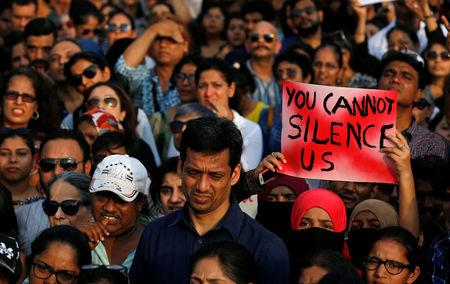 A woman holds a placard as she participates in a protest against the rape of an eight-year-old girl in Kathua near Jammu, and a teenager in Unnao, Uttar Pradesh state, in Mumbai, India, April 15, 2018. REUTERS/Danish Siddiqui