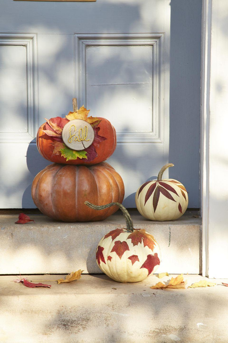 """<p>Nestled in the crook of a covered front porch, these simple and elegant gourds are decorated with leaves and a few easy-to-find craft supplies.</p><p><strong>To make:</strong><strong><br></strong></p><p><strong>Fall Lettering:</strong> Attach leaves, in a wreath shape, to a pumpkin with flat head push pins. Use a pencil to lightly draw the word """"fall"""" on a small wood round. Attach thin leather cording or twine over the drawing with hot glue. Hot glue wood round to the pumpkin over the center of the leaves.</p><p><strong>Leaf Covered: </strong>For one season pumpkins attach leaves from the yard with spray adhesive in a loose pattern. If you want to keep the pumpkin from year to year attach preserved leaves to a fake pumpkin. </p>"""