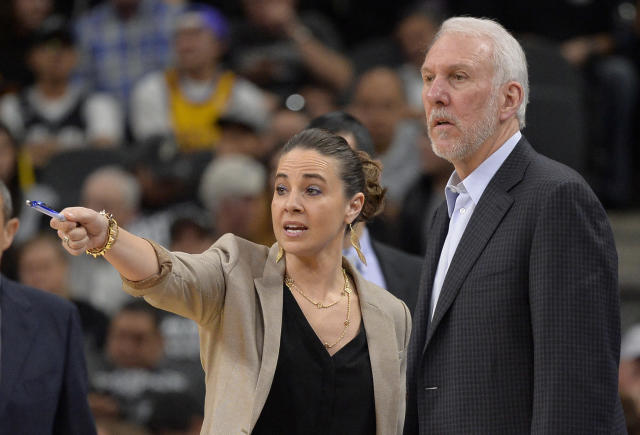 "<a class=""link rapid-noclick-resp"" href=""/nba/teams/sas"" data-ylk=""slk:San Antonio Spurs"">San Antonio Spurs</a> assistant coach Becky Hammon (L) talks to Spurs head coach Gregg Popovich on the court during a timeout in the second half of an NBA basketball game against the Los Angeles Lakers in San Antonio. (AP Photo)"