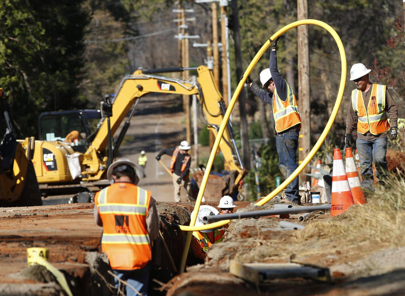 FILE - In this Oct. 18, 2019, file photo, Pacific Gas and Electric Company workmen bury utility lines in Paradise, Calif. California regulators are voting Wednesday, Nov. 13, on whether to open an investigation into pre-emptive power outages that blacked out large parts of the state for much of October as strong winds sparked fears of wildfires. PG&E officials insisted on the shut-offs to prevent wildfires but a parade of public officials complained the company botched its communications. (AP Photo/Rich Pedroncelli, File)
