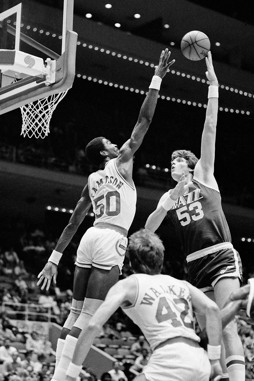 FILE - In this Nov. 11, 1983, file photo, Utah Jazz center Mark Eaton , right, puts a hook shot up and over the outstretched hand of Houston Rocket center Ralph Sampson during the first period of an NBA basketball game at the Summit in Houston. Eaton, the 7-foot-4 shot-blocking king who twice was the NBA's defensive player of the year during his career with the Utah Jazz, has died, the team said Saturday, May 29, 2021. He was 64. (AP Photo/R.J. Carson, File)