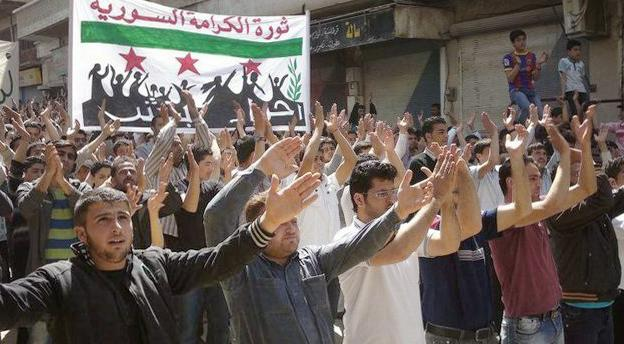"""In this citizen journalism image provided by the Local Coordination Committees in Syria and taken on Friday, April 6, 2012, Syrians chant slogans during a demonstration in Idlib, north Syria. A U.N.-brokered peace deal for Syria appeared to collapse Sunday April 8, 2012 as the government made a new demand that its opponents provide """"written guarantees"""" to lay down their weapons before regime forces withdraw from cities, a call swiftly rejected by the country's main rebel group. The banner with the Syrian revolutionary flag on it and Arabic writing reads, """"dignity revolution in Syria."""" (AP Photo/Local Coordination Committees in Syria) THE ASSOCIATED PRESS IS UNABLE TO INDEPENDENTLY VERIFY THE AUTHENTICITY, CONTENT, LOCATION OR DATE OF THIS HANDOUT PHOTO"""