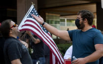 A man gestures, left, after a counterprotester crossed the street to make his case, during a rally held by Republican Reps. Marjorie Taylor Greene and Matt Gaetz near City Hall in Riverside, Calif., Saturday, July, 17, 2021. (Cindy Yamanaka/The Orange County Register via AP)