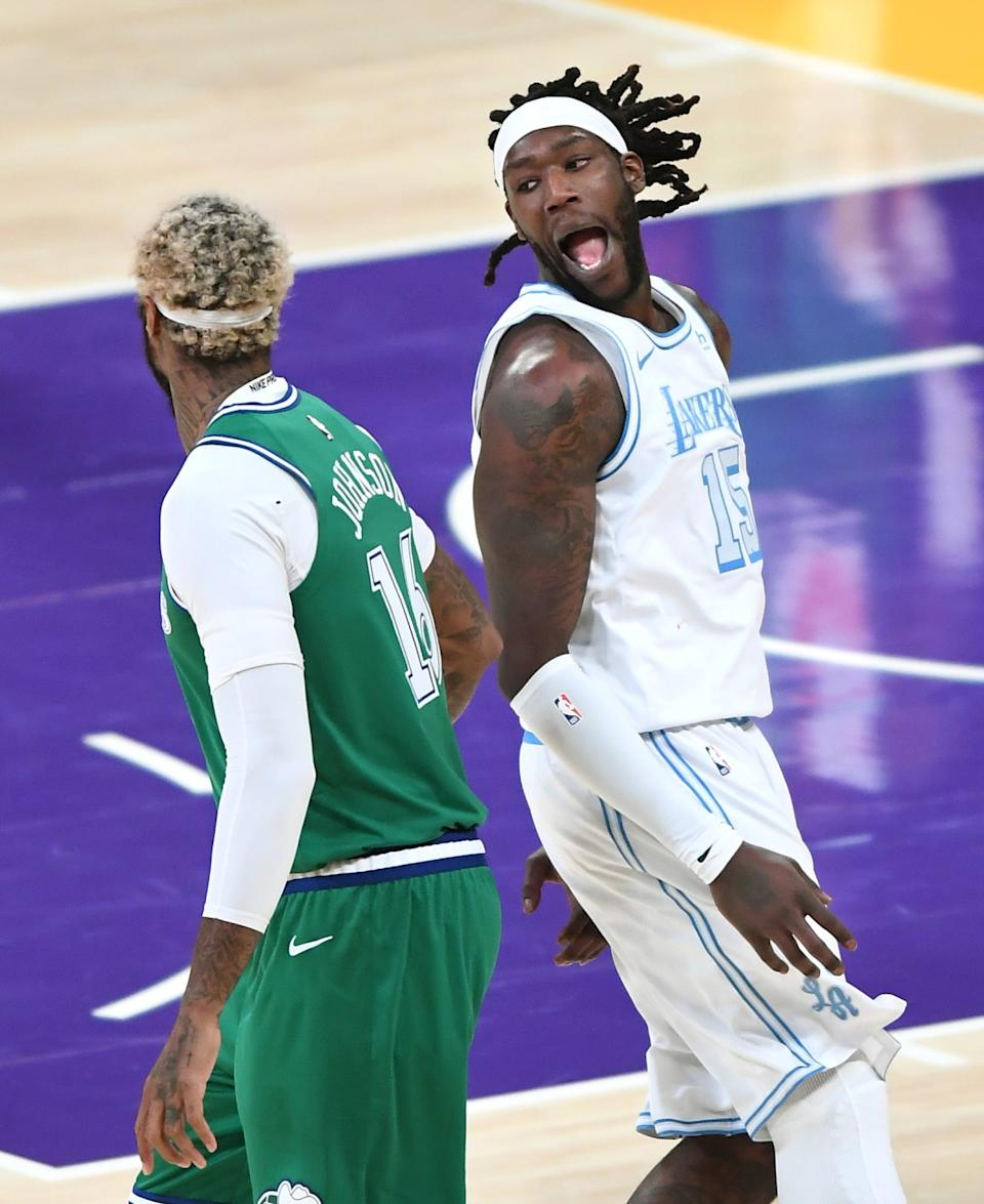 Lakers forward Montrezl Harrell celebrates after scoring in front of Mavericks forward James Johnson.