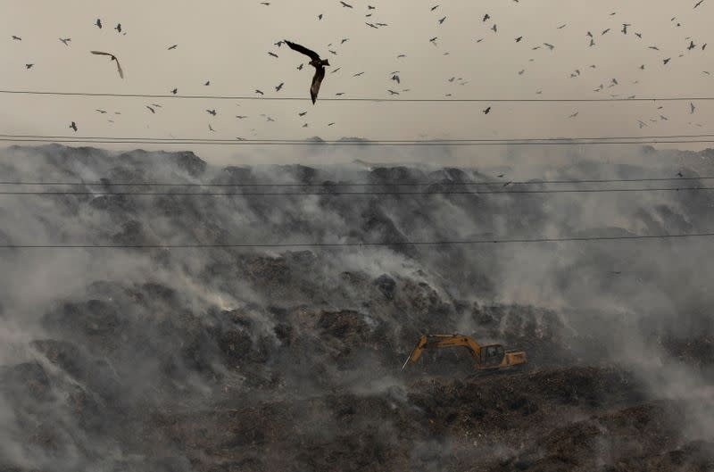 An excavator tries to contain the fire as smoke billows from burning garbage at the Ghazipur landfill site in New Delhi