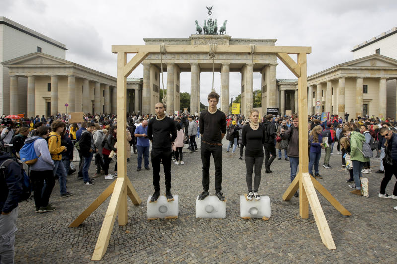 Three persons stand on ice blocks under gallows to protest against the climate policy prior to a 'Friday for Future' climate protest in front of the Brandenburg Gate in Berlin, Germany, Friday, Sept. 20, 2019. Protests of the 'Friday For Futurte' movement against the increase of carbon dioxide emissions are planned Friday in cities around the globe. In the United States more than 800 events were planned Friday, while in Germany more than 400 rallies are expected. (AP Photo/Markus Schreiber)