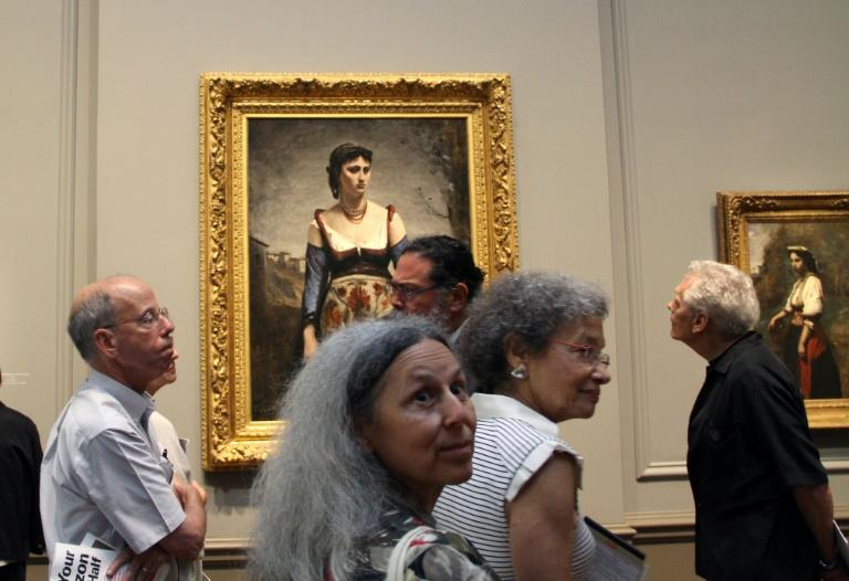 """Visitors look at Jean-Baptiste-Camille Corot's """"Agostina"""" (1866) at the National Gallery of Art in Washington on September 5, 2018"""