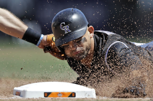 Colorado Rockies' Gerardo Parra is tagged by San Francisco Giants third baseman Evan Longoria at third base after a single by Trevor Story during the fifth inning of a baseball game Saturday, May 19, 2018, in San Francisco. (AP Photo/Marcio Jose Sanchez)
