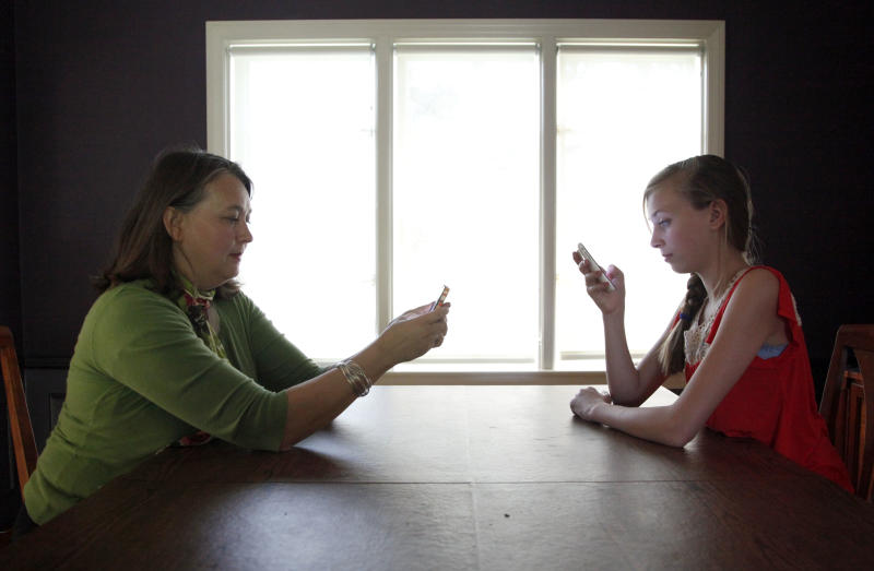 In this Thursday, May 24, 2012 photo, Anna Schiferl, right, and her mother, Joanna, pose for a photograph holding their cell phones in the dining room of their LaGrange, Ill. home. Statistics from the Pew Internet & American Life Project show that, these days, many people with cell phones prefer texting over a phone call. It's not always young people, though the data indicates that the younger you are, the more likely you are to prefer texting. But many experts say the most successful communicators will, of course, have the ability to do both talk or text, and know the most appropriate times to use those skills. (AP Photo/Charles Rex Arbogast)