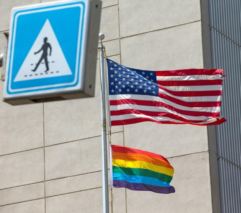 A gay pride flag is raised next to the US flag at the US embassy in Israel during a June 2014 Pride parade in Tel Aviv