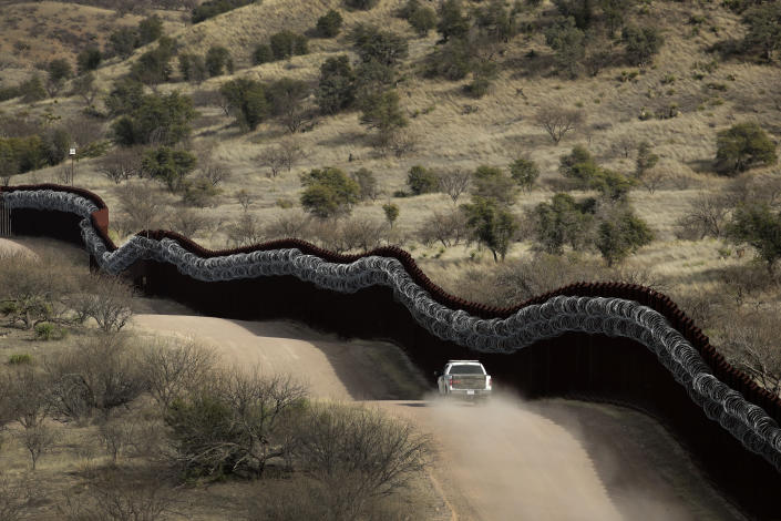 FILE - In this March 2, 2019, file photo, a Customs and Border Control agent patrols on the U.S. side of a razor-wire-covered border wall along the Mexico east of Nogales, Ariz. U.S. officials say attempted border crossings by migrants traveling in family groups that include children increased in June by a quarter over the previous month amid rising summer temperatures in the inhospitable deserts and mountain terrain of the American Southwest. (AP Photo/Charlie Riedel,File)