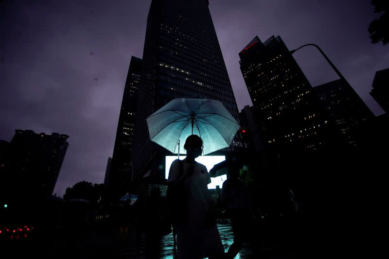 A woman walks with an umbrella in Lujiazui financial district in Pudong