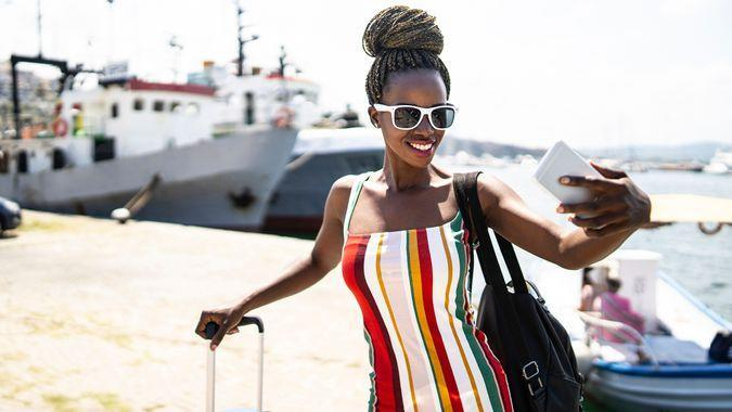 Front view of elegant african woman taking selfie at habor.