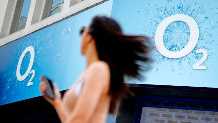 A woman holds a mobile phone as she walks past an O2 mobile phone store