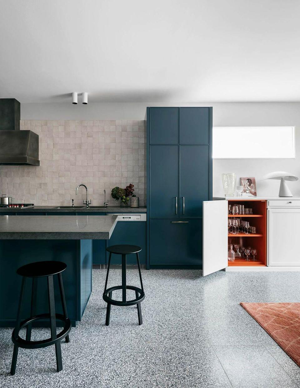 "<p>An inky, marine blue will ground a kitchen in an open space and feel more formal than a light color without being as moody and as dark as black. We also love the idea of painting the interior cabinets a color that corresponds with an accent piece in the room, like this orange cabinet designed by <a href=""https://arentpyke.com/"" rel=""nofollow noopener"" target=""_blank"" data-ylk=""slk:Arent & Pyke"" class=""link rapid-noclick-resp"">Arent & Pyke</a> to match the carpet.</p>"