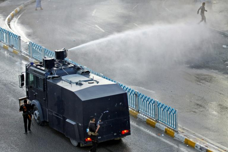 Demonstrators are sprayed with water cannon by the Iraqi security forces during protests in the central shrine city of Najaf on July 14, 2018