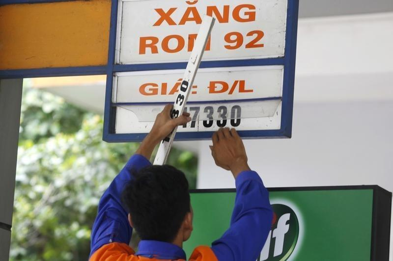 An employee changes a price sign at a petrol station in Hanoi