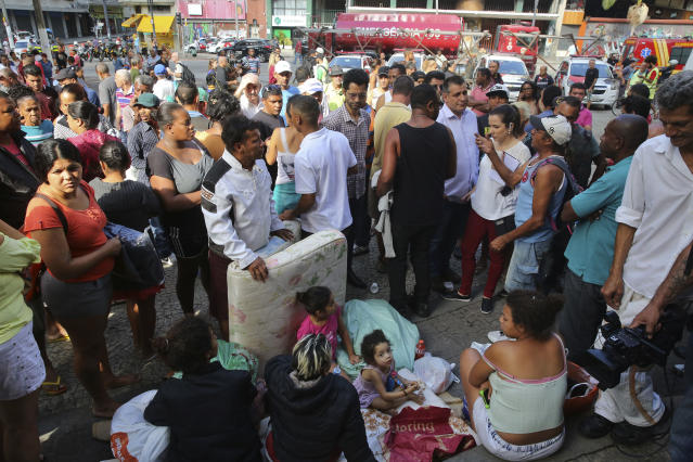 <p>Displaced occupants of a collapsed building sit and gather on the sidewalk in Sao Paulo, Brazil, Tuesday, May 1, 2018. (Photo: Andre Penner/AP) </p>