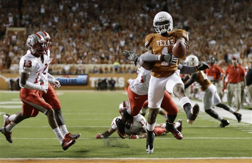 Texas' Mike Davis (1) is pulled down by New Mexico's Joseph Harris (44) as he scores a touchdown during the second quarter of an NCAA college football game on Saturday, Sept. 8, 2012, in Austin, Texas. (AP Photo/Eric Gay)