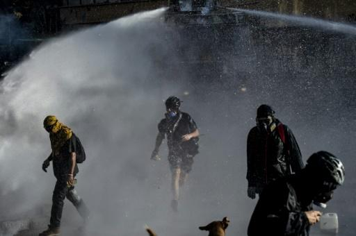 Demonstrators clash with the police during Monday night's protest in Santiago