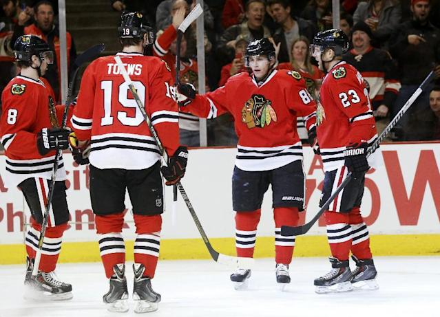 Chicago Blackhawks right wing Patrick Kane (88) celebrates his goal with Nick Leddy (8), Jonathan Toews (19) and Kris Versteeg (23) during the second period of an NHL hockey game against the New Jersey Devils, Monday, Dec. 23, 2013, in Chicago. (AP Photo/Charles Rex Arbogast)