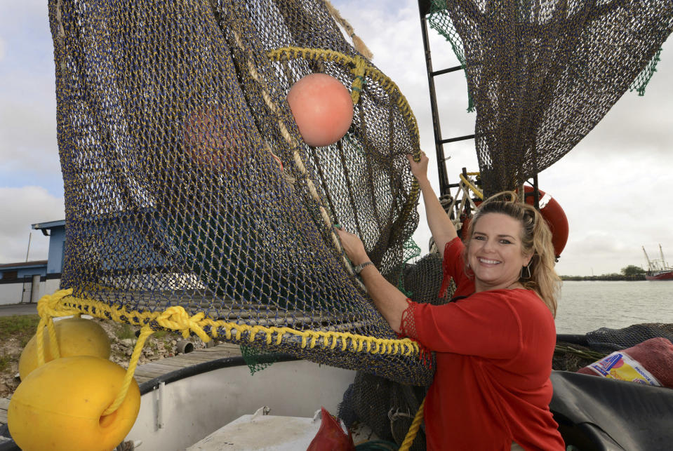 "FILE - In this Friday, Dec. 5, 2014 file photo, Andrea Hance, Texas Shrimp Association executive director, poses with a TED, or turtle excluder device, on board a shrimp boat at the Brownsville Shrimp Basin in Brownsville, Texas. Federal regulators have vastly scaled back a plan to make more shrimpers include escape hatches for small sea turtles in their nets. A conservation group, the Center for Biological Diversity, calls it ""a dangerous departure."" The proposed rule would have required about 5,800 inshore shrimp boats to use the escape hatches, called turtle excluder devices or TEDs. The rule made public Thursday, Dec. 19, 2019, applies to fewer than 1,100. (Brad Doherty/The Brownsville Herald via AP, File)"